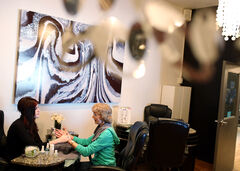 Straight Up Salon nail technician Morgan Rutledge gives Nearly New Shop volunteer Janice Jones a manicure.