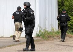 Members of Brandon Police Service's Tactical Response Unit and other members search for a suspect along Rosser Avenue after a chase on Thursday afternoon. A suspect crashed their vehicle into a barrier in the CP Rail yard.