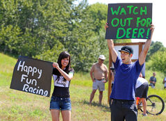 Aaron Check and his wife Sam hold up signs prior to a Manitoba Cycling Association sanctioned race, Sunday afternoon at the new mountain biking trail on Hanbury Hill near the Sportsplex.