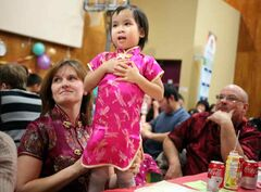 Brandonite Christine Burton plays with daughter Tahlia as she and husband Todd take in the Chinese New Year Celebration at Knox United Church on Saturday evening. The couple adopted Tahlia, who was born in southern China, two years ago.