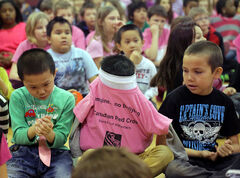A student hides his head in his anti-bullying awareness T-shirt during a Day of Pink rally at New Era School on Wednesday.
