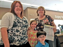 Karen Goodfellow, right, celebrates her big lottery win with her daughter Loni Thompson, left, and grandchildren Emmalie Thompson and Aiden Thompson.