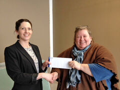 Marla Somersall, executive director of Samaritan House Ministries, right, accepts a donation from Westoba Credit Union marketing co-ordinator Pennie Nylen.