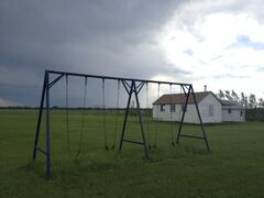 In this file photo, a swing set stands empty outside a home at a Manitoba Old Order Mennonite community last summer. Child and Family Services apprehended the community's children due to allegations of physical abuse related to extreme discipline.  Cutline 2: A swing set stands empty outside the one-room school house at a Manitoba Old   Order Mennonite community. Child and Family Services has apprehended the community's children due to allegations of physical abuse related to