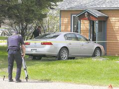 RCMP officers at the scene of the killing in MacGregor Monday afternoon.