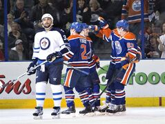 Winnipeg Jets' Dustin Byfuglien (33) looks on as Edmonton Oilers' Andrew Ference (21), Jordan Eberle (14) and Ales Hemsky (83) celebrate a goal during first period NHL hockey action in Edmonton, Alta., on Monday December 23, 2013. THE CANADIAN PRESS/Jason Franson