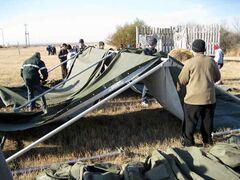 Cadets work together in setting up a modular tent.