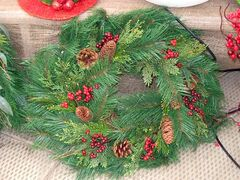 A typical Christmas wreath decorated with cones and red artificial berries.