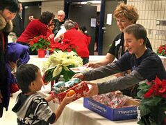 Volunteers hand out presents to guests at the 28th annual Westman and Area Traditional Christmas Dinner at the Keystone Centre in Brandon on Tuesday. The event lasted from noon to 6 p.m., with meals also being delivered to shut-ins.