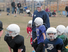 New Winnipeg Blue Bombers head coach Mike O'Shea chats with a young Westman Youth Football League player during Thursday night's practice at the Crocus Plains high school field.