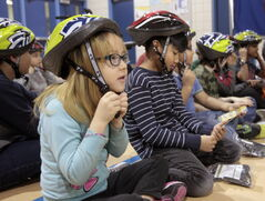 Jolene Clarke, 7, and fellow students at Meadows West School received bicycle helmets and instruction on how to wear them Tuesday.