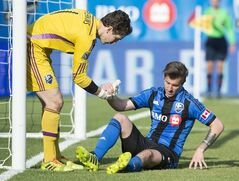 Montreal Impact goalkeeper Troy Perkins, left, helps teammate Jeb Brovsky up off the turf during second half MLS soccer action against Sporting Kansas City in Montreal, Saturday, May 10, 2014. THE CANADIAN PRESS/Graham Hughes