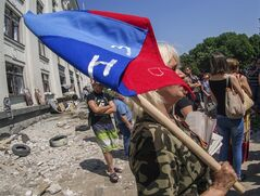 "A woman holds a flag of the self-proclaimed Luhansk republic during a rally against the inauguration of Ukraine's new president in Luhansk, Ukraine, Saturday, June 7, 2014. Ukraine's new president , Petro Poroshenko, on Saturday called for dialogue with the country's east, gripped by a violent separatist insurgency, and for armed groups to lay down their weapons but said he won't talk with rebels he called ""gangsters and killers."" (AP Photo/Igor Golovniov)"