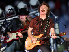 Doobie Brothers members Tom Johnston, right, and Patrick Simmons, back left, perform during halftime at the Orange Bowl NCAA college football game in Miami in 2009.
