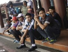 In this March 11, 2014 photo, Burmese migrants who were trafficked wait for their bus as they are about to return to their country, at Soekarno-Hatta International Airport in Jakarta, Indonesia. Tens of thousands of invisible migrants are trafficked annually through Thailand, Southeast Asia's second-largest economy. (AP Photo/Dita Alangkara)