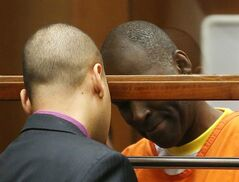 Actor Michael Jace, right, talks with his attorney Jason Sias in Los Angeles Superior Court during a hearing of the charge that he murdered his wife, Friday, Aug. 1, 2014. Jace waived his right to a preliminary hearing, which means the case will proceed to trial without an initial presentation of evidence to a judge. Jace played a police officer on