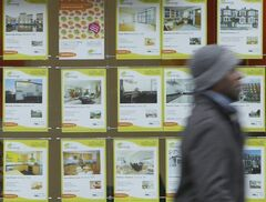 FILE - In this Thursday, Jan. 27, 2011 file photo, a man walks past an estate agents window displaying properties for sale, in Chiswick a suburb of London. Concerns are mounting that Britain's housing market is overheated after London house prices rose almost 19 percent in the past 12 months. Bank of England Governor Mark Carney recently described the situation as the greatest risk to the domestic economy. The International Monetary Fund is worried. Ditto the European Union's executive commission. The pressure is on to act now rather than risk having it all come crashing down later, dragging Britain back into recession. A committee set up in the wake of the financial crisis to handle threats to domestic financial stability is due to issue its recommendations on Thursday, June 26, 2014 and economists suggest it will take action to cool the market. (AP Photo/Alastair Grant, File)