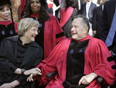 Harvard University President Drew Faust, left, speaks with former President George H. W. Bush, right, before Harvard commencement ceremonies, Thursday, May 29, 2014, in Cambridge, Mass. Bush was presented with with an honorary doctor of laws degree during the ceremonies. Chilean author Isabel Allende, top left, and singer Aretha Franklin, behind center left, look on. (AP Photo/Steven Senne)