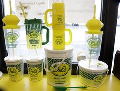 This April 30, 2014 photo shows drink containers in the window of a Del's Lemonade location in Cranston, R.I. The lemony slush, made of water, sugar, lemon juice and chunks of rind, has become a cultural icon in the state. It's not unusual to see the trucks or carts at wedding receptions, birthday parties, bar mitzvahs, and troop deployments and homecomings. (AP Photo/Steven Senne)