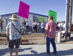 Dale Brown, left, and John Hultberg protest the opening of Altitude, a marijuana store as customers wait for the shop to open in Prosser, Wash., Tuesday, July 8, 2014. It was the first day marijuana could be sold legally in Washington state. Crawford, of Benton City, was purchasing the marijuana for recreational use. (AP Photo/Yakima Herald-Republic, Gordon King)