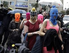 Five women wearing balaclavas, two of whom are members of the Russian punk group Pussy Riot, make their way through a crowd after they were released from a police station, Tuesday, Feb. 18, 2014, in Adler, Russia. No charges were filed against the Pussy Riot members Nadezhda Tolokonnikova, in the blue balaclava, and Maria Alekhina, in the pink, who were held along with several other people near the city's ferry terminal. (AP Photo/Morry Gash)
