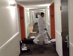A forensic identification officer walks between two rooms at the Motel 6 on the Trans-Canada Highway in Brandon in this still from a video. A man has been charged after a reported stabbing death on Wednesday evening.