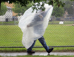 Jordan Stremel takes cover beneath some plastic sheeting while walking down Sixth Street on a rain-drenched Thursday afternoon.