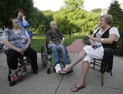 This Monday, June 16, 2014 photo shows Diane Conrad, left to right, Cyndy Stapleton, Bill Palmisano, and Melinda Elkins Dawson talking in North Canton, Ohio. A northern Georgia doctor running off-the-books adoptions in the 1950s and '60s placed infants with out-of-state parents who paid hundreds of dollars and were listed on records as the children's real parents. Now some of those adoptees are doing fresh DNA testing in hopes of identifying biological relatives. (AP Photo/Tony Dejak)