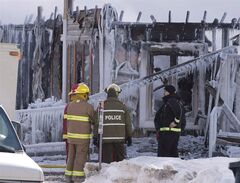 Police and firefighters survey the damage after a fatal fire at a seniors residence in L'Isle-Verte, Que., Thursday, January 23, 2014. The Quebec government is calling an inquiry into the fire that killed 32 people at the seniors' residence. The inquiry will be headed by longtime coroner Cyrille Delage. THE CANADIAN PRESS/Jacques Boissinot