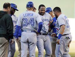 Toronto Blue Jays' Edwin Encarnacion, center right, is assisted off the field after tripping while running to first base in the first inning of a baseball game against the Oakland Athletics on July 5, 2014, in Oakland, Calif. Edwin Encarnacion rehabs with the Buffalo Bisons as his return to the Blue Jays' lineup inches closer. THE CANADIAN PRESS/AP, Ben Margot