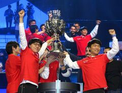 FILE - In this Oct. 4, 2013, file photo, members of South Korea's SK Telecom T1 team celebrate with their trophy after defeating China's Royal Club at the League of Legends Season 3 World Championship Final in Los Angeles. Robert Morris University Illinois, a small private university in Chicago, is offering hefty scholarships for players of League of Legends, which has become one of the most popular games for organized team competitions. The university said it recognizes the growing legitimacy of what are known as