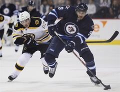 Boston Bruins' Brad Marchand (63) chases down Winnipeg Jets' Evander Kane (9) during second period NHL action in Winnipeg on Thursday, April 10, 2014. Kane says he did throw three punches but only in defence as he was attacked in Vancouver by a man now suing him for assault. THE CANADIAN PRESS/John Woods