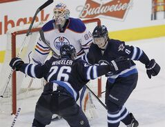 Winnipeg Jets' Blake Wheeler (26) and Jacob Trouba (8) celebrate Trouba's game winning goal against Edmonton Oilers' goaltender Ilya Bryzgalov (80) during overtime NHL action in Winnipeg on Saturday, January 18, 2014. THE CANADIAN PRESS/John Woods