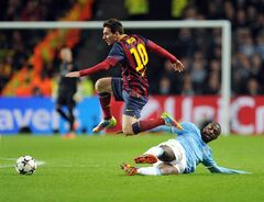 Manchester City's Yaya Toure, right, attempts a tackle Barcelona's Lionel Messi during their Champions League Round of 16 soccer match at the Etihad Stadium in Manchester, England, Tuesday, Feb. 18, 2014. (AP Photo/Clint Hughes)