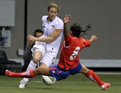 FILE - In this Jan. 27, 2012, file photo, United States' Kelly O'Hara (5) fights for control of the ball with Costa Rica's Daniela Cruz (8) during the first half of CONCACAF women's Olympic qualifying soccer game action at B.C. Place in Vancouver, British Columbia. The law firm that represents soccer players who object to an artificial turf surface at the Women's World Cup says a FIFA-commissioned survey of players shows that 77 percent feel major tournaments should be played on natural grass. But that wasn't enough to sway organizers to let the women play on grass.(AP Photo/The Canadian Press, Jonathan Hayward, File)