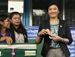 FILE - In this Feb. 2, 2014 file photo, Thai Prime Minister and Pheu Thai party leader Yingluck Shinawatra, right, smiles as she poses before casting her ballot for the general election at a polling station in Bangkok. Thailand's government and the state Election Commission have agreed to hold new general polls on July 20. The commission announced the date after meeting Wednesday, April 30 with Yingluck and other officials. (AP Photo/Wally Santana, File)