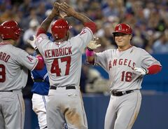 Los Angeles Angels' Hank Conger, right, is congratulated by teammates Efren Navarro and Howie Kendrick after hitting a three-run homerun off Toronto Blue Jays pitcher Marcus Stroman during sixth inning AL action in Toronto on Sunday, May 11, 2014. THE CANADIAN PRESS/Frank Gunn