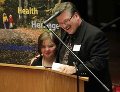 Ken McKenzie-Cochrane, with daughter Mia, speaks to the audience gathered in city hall for the 21st annual grant presentation ceremony for the Brandon Area Community Foundation. McKenzie-Cochrane represented the Brandon Film Festival, which organizes movies at the Evans Theatre and needs funding to convert to a digital projection system.