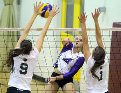 Vincent Massey's Tristan Neudorf (centre) slams the ball at Neelin's Alison Quiring (left) and Amy Gordon during the Top 8 Debate varsity girls volleyball tournament, Saturday afternoon.