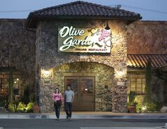 In this May 22, 2014 photo, patrons exit an Olive Garden Restaurant, a Darden restaurant brand, in Short Pump, Va. Darden's fiscal fourth-quarter profit dropped 35 percent, dragged down by charges and costs tied to its strategic plan to reshape the restaurant company. (AP Photo/Steve Helber)