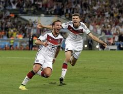 Germany's Mario Goetze (19) celebrates with Thomas Mueller after scoring his side's first goal in extra time against Argentina's goalkeeper Sergio Romero during the World Cup final soccer match between Germany and Argentina at the Maracana Stadium in Rio de Janeiro, Brazil, Sunday, July 13, 2014. (AP Photo/Felipe Dana)