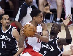 Toronto Raptors guard DeMar DeRozan, centre, looks for a pass against Brooklyn Nets forward Kevin Garnett (2) and Shaun Livingston (14) during first half NBA game seven playoff basketball action in Toronto on Sunday, May 4, 2014. The Raptors will play pre-season games in Vancouver and Montreal in October. THE CANADIAN PRESS/Nathan Denette
