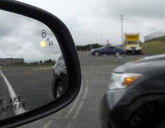 FILE - This May 22, 2012 file photo shows a demonstration of a side mirror warning signal in a Ford Taurus at an automobile testing area in Oxon Hill, Md. The Obama administration said Monday it is taking a first step toward requiring that future cars and light trucks be equipped with technology that enables them to warn each other of potential danger in time to avoid collisions. A research report released by the National Highway Traffic Safety Administration estimates that the technology could eventually prevent 592,000 left-turn and intersection crashes a year, saving 1,083 lives. The agency said it will begin drafting rules to require the technology in new vehicles. (AP Photo/Susan Walsh, File)