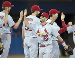 St. Louis Cardinals Matt Carpenter (13) celebrates with teammates after defeating the Toronto Blue Jays 5-0 in interleague action in Toronto on Sunday June 8, 2014. THE CANADIAN PRESS/Frank Gunn