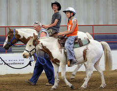 Zachary McIntosh (back) and Matthew Gagnon ride horses during a visit by special-needs children organized by the Society for Manitobans with Disabilities on Monday afternoon at the Keystone Centre.