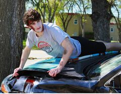 École secondaire Neelin High School student Jacob Thomson situates himself on the hood of the car during a mock crash, organized by Mothers Against Drunk Driving, outside the school on Thursday morning. The display aimed to show students the consequences of driving while under the influence.