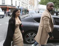FILE - In this May 21, 2014 file photo, Kim Kardashian and U.S rap singer Kanye West arrive at a luxury shop in Paris. Before exchanging vows, the two held court in Paris, paraded for photographers and posted photos on Instagram from fashion designer Valentino's 17th-century Chateau de Wideville. There were costume changes, including a sexy open-front white number for the new Ms. Kardashian West. (AP Photo/Jacques Brinon, File)
