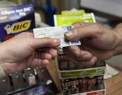 A consumer pays with a credit card at a store July 6, 2010 in Montreal. THE CANADIAN PRESS/Ryan Remiorz