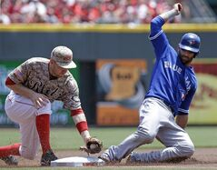 Toronto Blue Jays' Jose Bautista, right, advances safely to third base as Cincinnati Reds third baseman Todd Frazier applies the tag in the first inning of a baseball game on Sunday, June 22, 2014, in Cincinnati. Bautista advanced on a hit by Edwin Encarnacion. (AP Photo/Al Behrman)