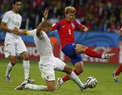 Algeria's Madjid Bougherra kicks the ball away from South Korea's Son Heung-min (9) during the group H World Cup soccer match between South Korea and Algeria at the Estadio Beira-Rio in Porto Alegre, Brazil, Sunday, June 22, 2014. (AP Photo/Jon Super)